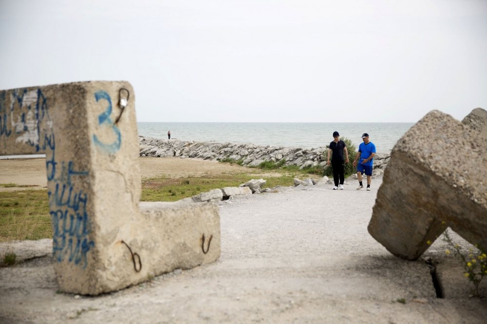 People walk and chat along the coast of the Caspian Sea in Caspiysk.