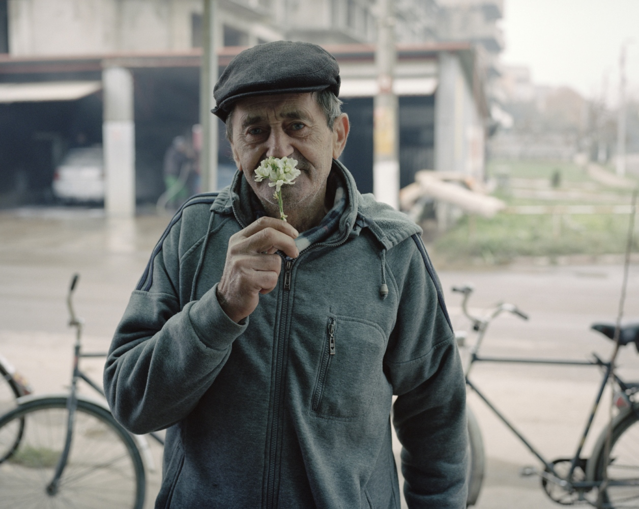 Romania, Zimnicea. An unemployed man smell a local flower. Most of the people of city emigrate in other European countries to find a job.During the1977 Romanian earthquakenot many buildings have been destroyed.Most of the destruction was actually done after the natural disaster by bulldozer, being ordered bycommunist authorities, as a means to create a town from scratch on a new design.Ten years later, the newly built infrastructure was falling apart due mainly to poor workmanship