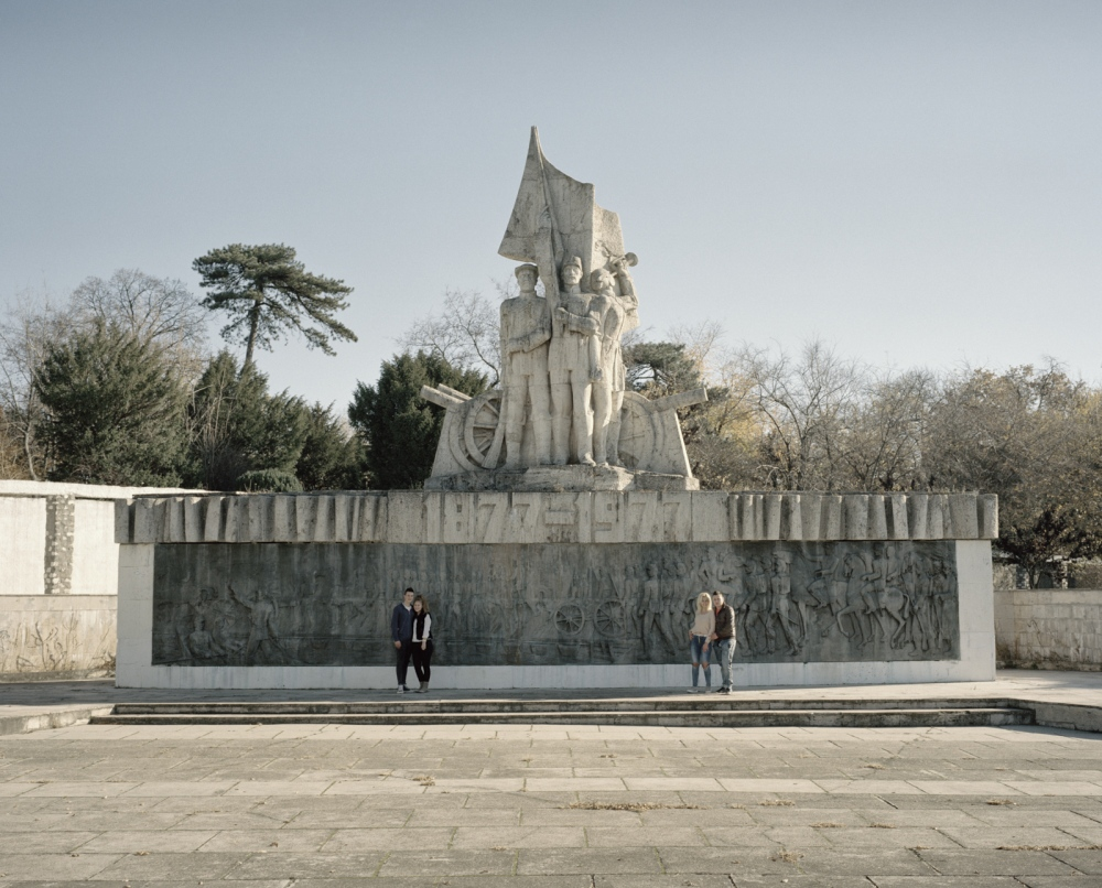 Romania, Calafat. Two teenagers couple pose in front of a communist style monument.