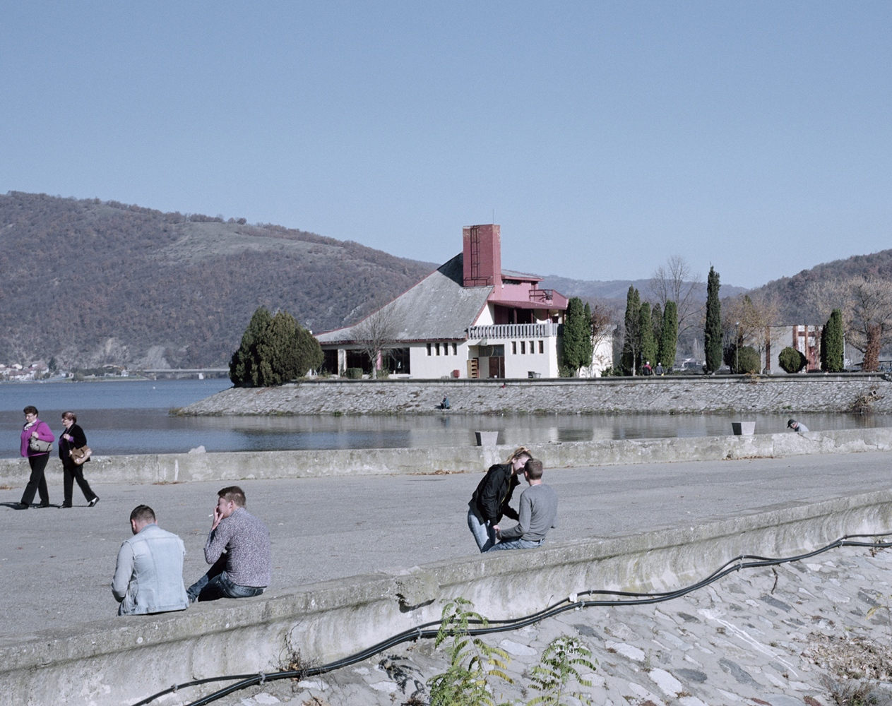 Romania, Orsova. Teenager chill out on the lake creted by a dam on the Danube River.
