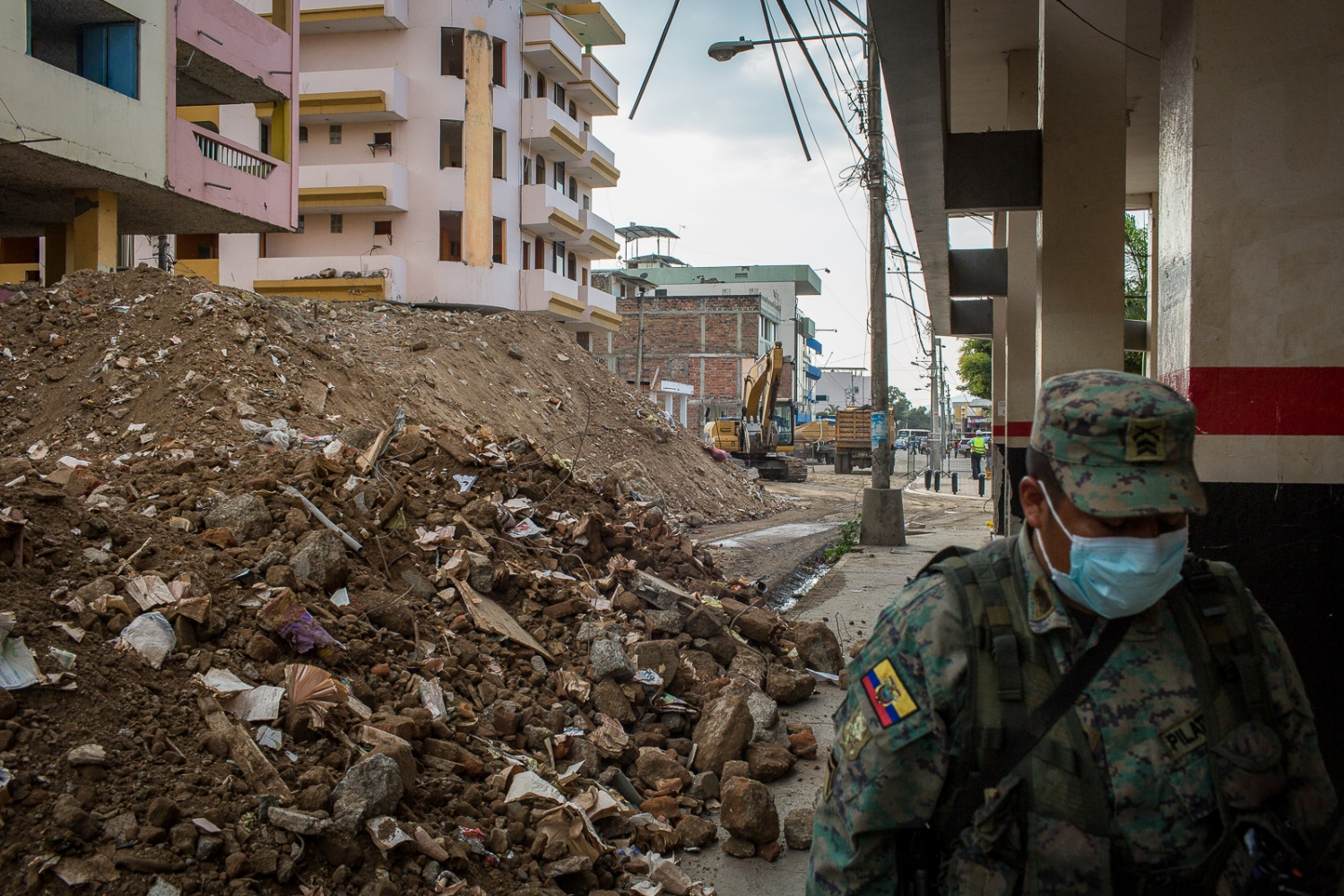 A soldier passes by some derelict buildings in Portoviejo's centre. He uses a mask to avoid breathing the dust that fills the air, after so many buildings collapsed. Portoviejo's town centre is closed to the public and secured by the army since most of its building were heavily damaged by the earthquake, turning it into a ground zero area.