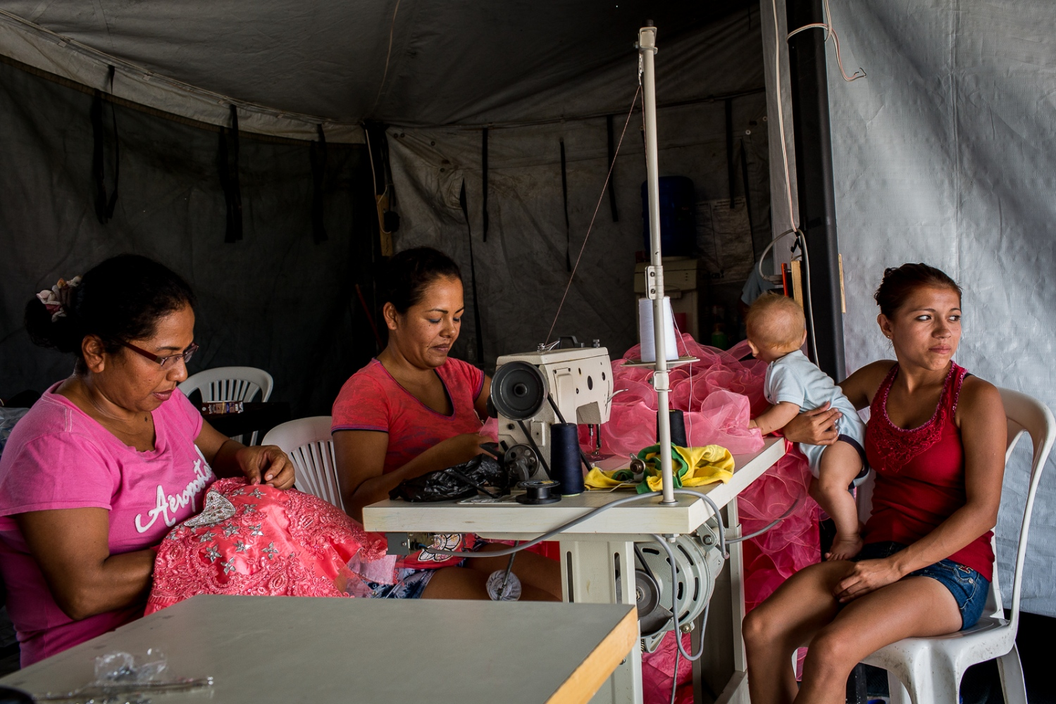 Miriam Zambrano (in the centre), 37, works on her sawing machine on a tent at the shelter located on the old airport, Portoviejo, Ecuador, with the help of another lady, while her daughter-in-law takes care of Miriam's grandson. Miriam managed to recover her sawing machine from the wreckage, and kept working as a dressmaker in order to sustain her six children, one daughter-in-law and one grandson. She is happy to be in the shelter and hopes that eventually she will get a house from the Government.