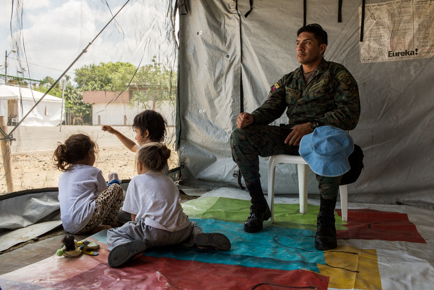 Corporal Quiroz of the Ecuadorian army, looks after some children while their mothers went to collect food on the communal kitchen of the shelter in Portoviejo. The shelters are managed and operated by the army and they try to help the families that live there and that have lost everything on the 16th April earthquake.