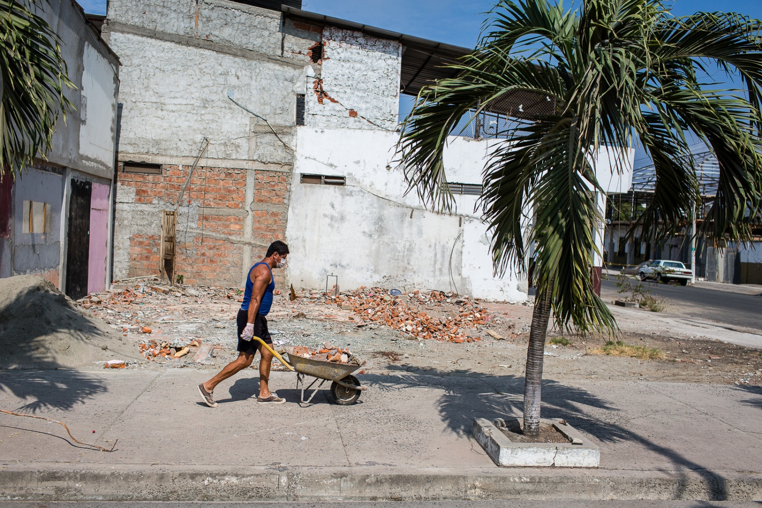 A man carries wreckage of the house he is rebuilding in Bahia de Caráquez. Many people don't believe they will get any Government help, so they have started to rebuild their houses by themselves.