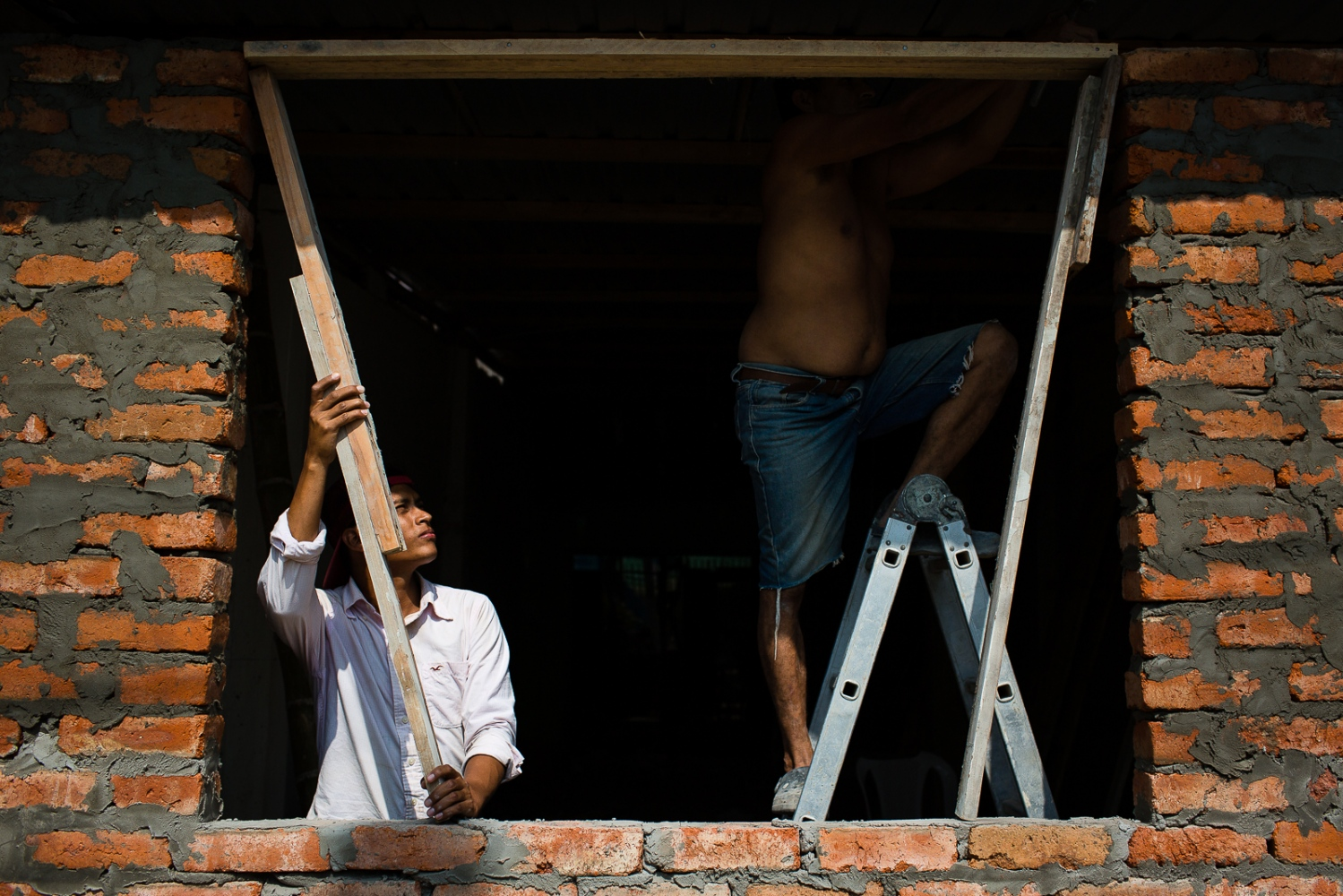 A son helps his father to rebuild a window of their home in Bahia de Caráquez. Many people don't believe they will get any Government help, so they have started to rebuild their houses by themselves.