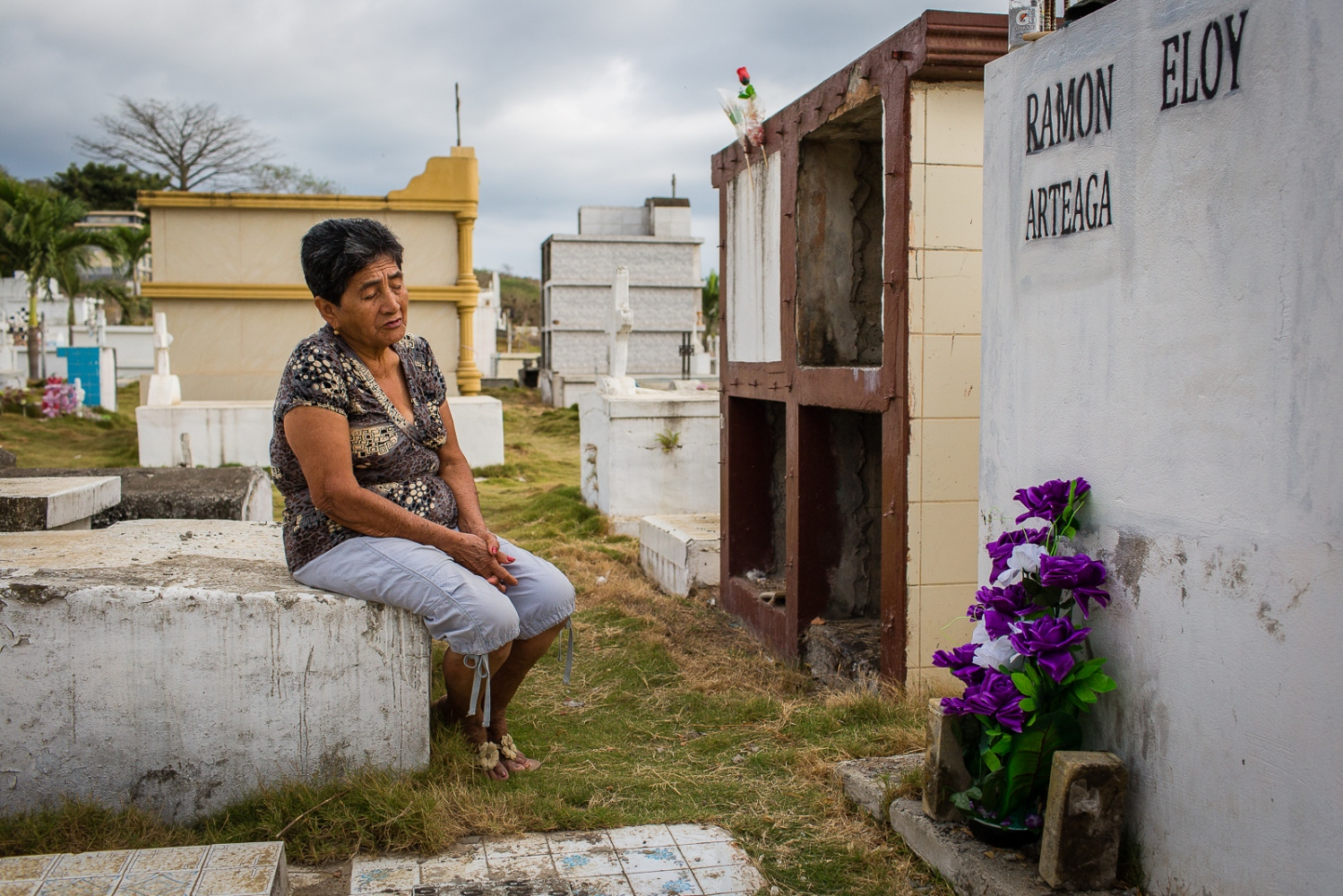 "Zoila Alciva, 78, visits her husband grave on the Jama cemetery. Her husband passed away after he was trapped between collapsing walls of their house during the 16th April earthquake. ""He was unable to escape because he was on a wheel chair"" says Zoila. She is critic of the Government because she didn't got any help; all the help came from family and friends."