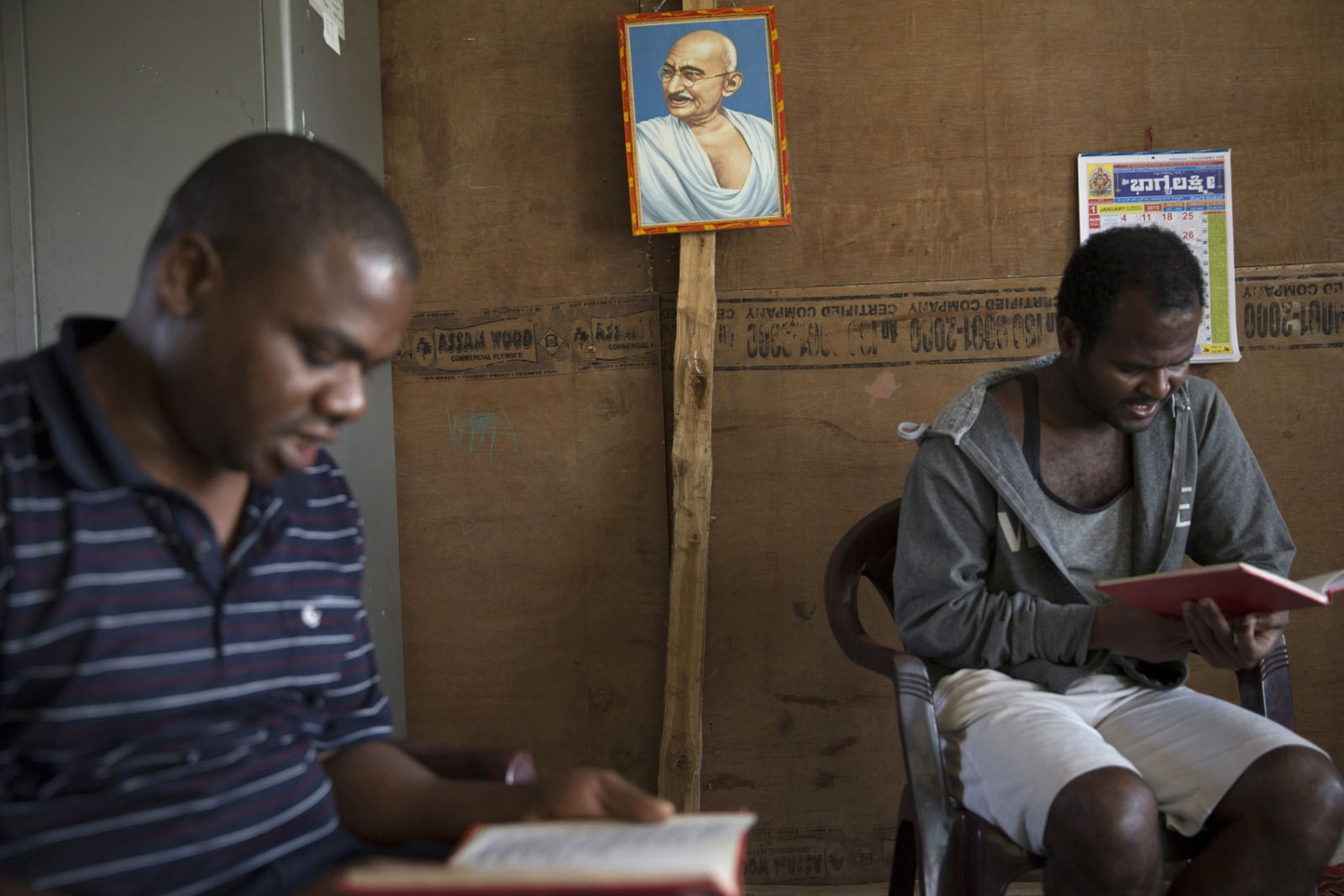 Head teacher Prakash Christian (left) and Mohan Sidi (right) take part in a bible reading session below a portrait of Mahatma Gandhi at a remote boarding school. Uttara Kannada, India