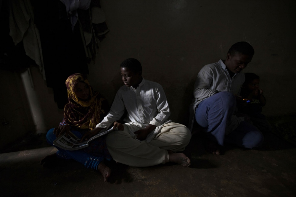 A Sheedi boy, as they are known in Pakistan, helps his sister with her homework using the light from the doorway during a power cut in a suburb of Karachi. Karachi, Pakistan