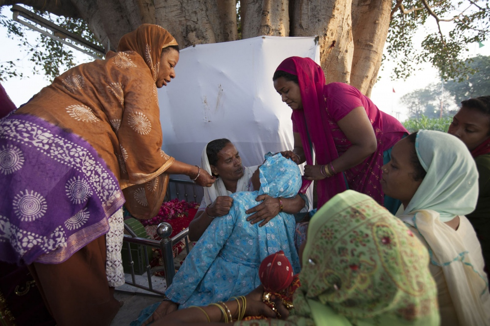 A Sidi women faints becoming possessed during the annual celebration of Urs, the anniversary of their saint Bava Gor, at the cities most holiest shrine for Sidi. They will hold this event every year and in this particular part of the shrine only women are allowed to worship. Jamnagar, India