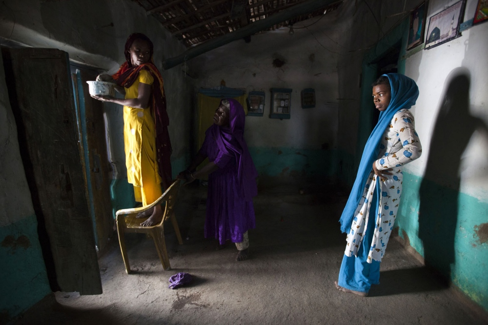 Sidi women prepare the interior wall of their house with a mixture of mud, cow dung and water. Bedi, India