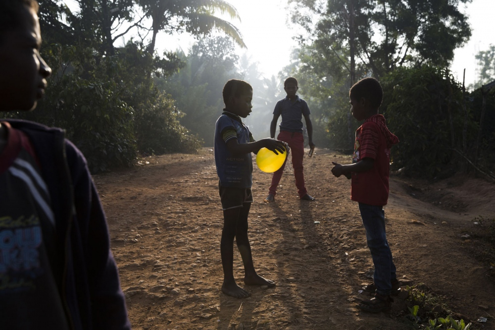 Sidi boys play with a balloon on the track outside their houses before they must walk to school. Uttara Kannada, India