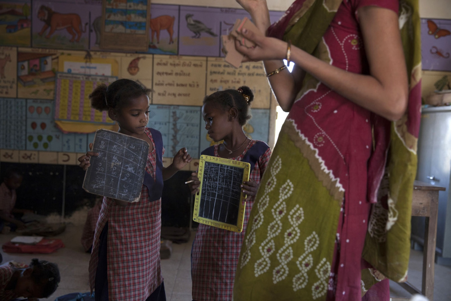 At the only school in Jambur two Sidi girls take their small blackboards to show the Indian teacher their work. The remote village of Jambur, located on the edge of the Gir forest, is almost 99% Sidi and has one of the highest concentrations of Sidi's in India. Jambur, India