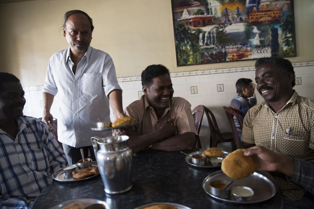 A group of Sidi elders laugh and eat breakfast at a local Indian restaurant in Yellapur. Uttara Kannada, India