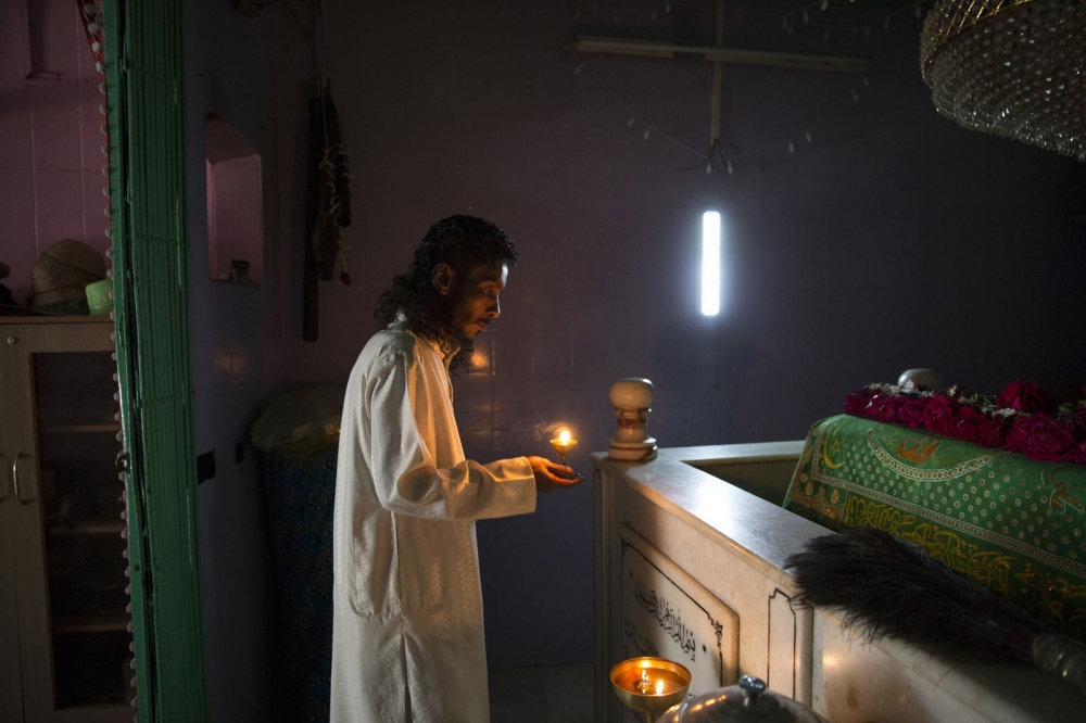 Imam Siddi Abdul Rauf l of the Siddi Mubarak Bava Gor Mosque lights a candle at the shrine of Bava Gor, the Sidi patron saint. Mumbai, India