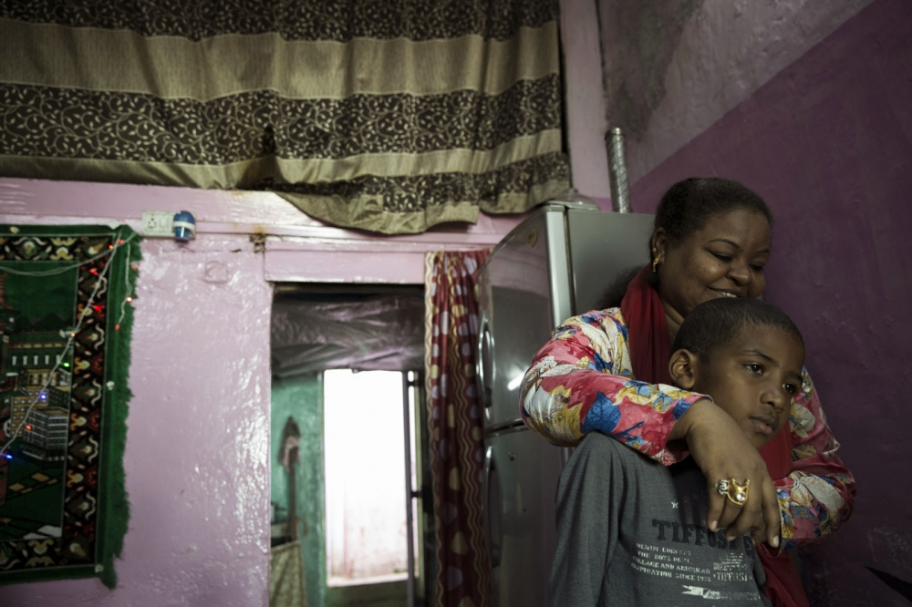 Heena Sidi hugs her son in their home in the large slum area of Narayan Nagar area of Mumbai. Mumbai, India