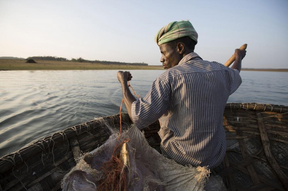 A Sidi man fishes in a reservoir in a traditional conical boat. Uttara Kannada, India