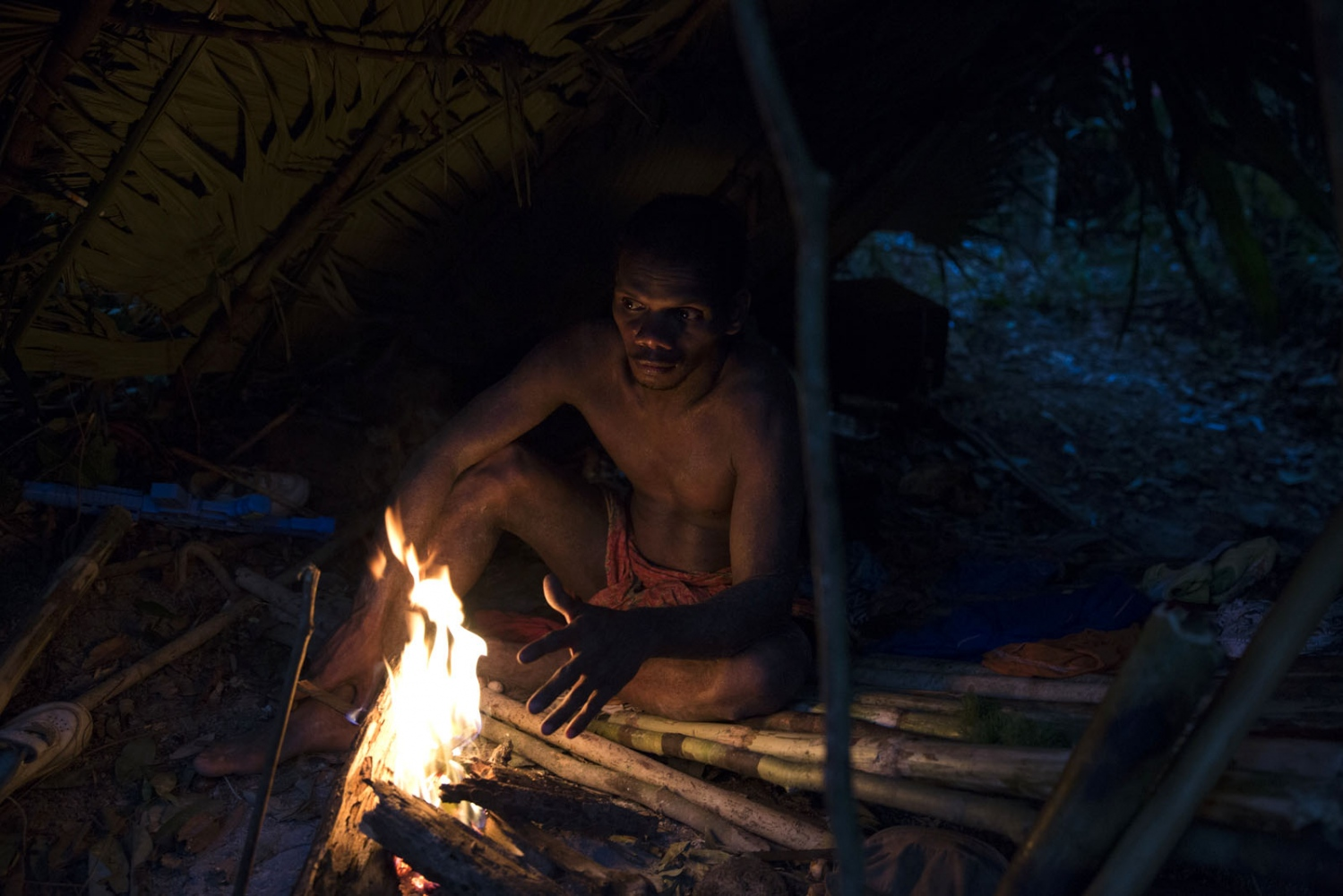 A Maniq man sits in his shelter at dusk. Many keep a fire burning inside their shelter 24 hours a day to indicate that it is occupied.  Pattalung - September 2016