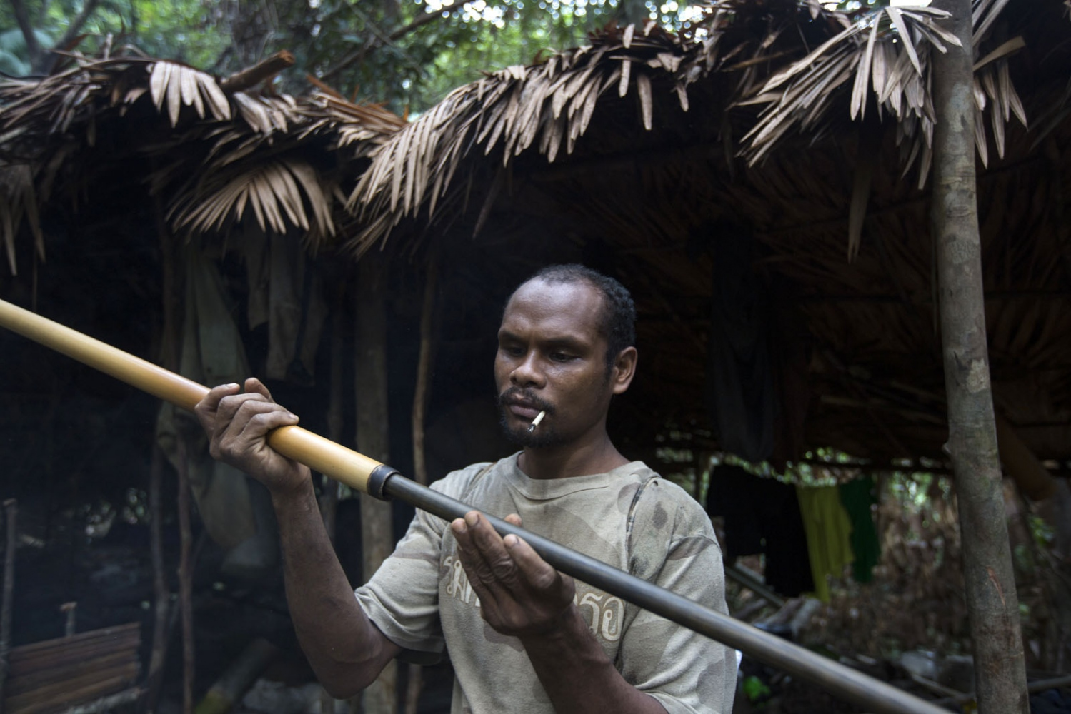 A village elder and expert hunter prepares his blow pipe for a hunt which often takes days. Satun - September 2016