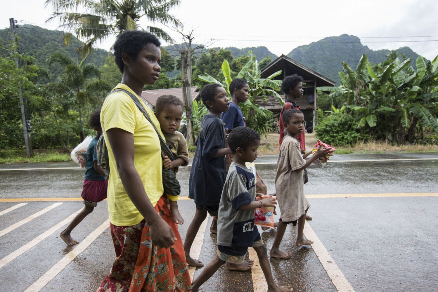 A group of Maniq youngsters walk bare-footed along a road to buy food from a shop in a nearby village. Satun - September 2016