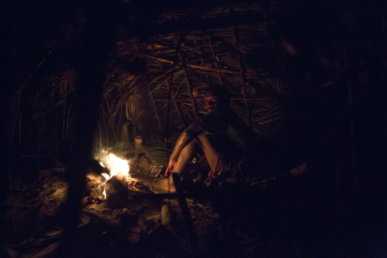A Maniq man called Yaaw sits inside his shelter at night ready to sleep. Satun - September 2016