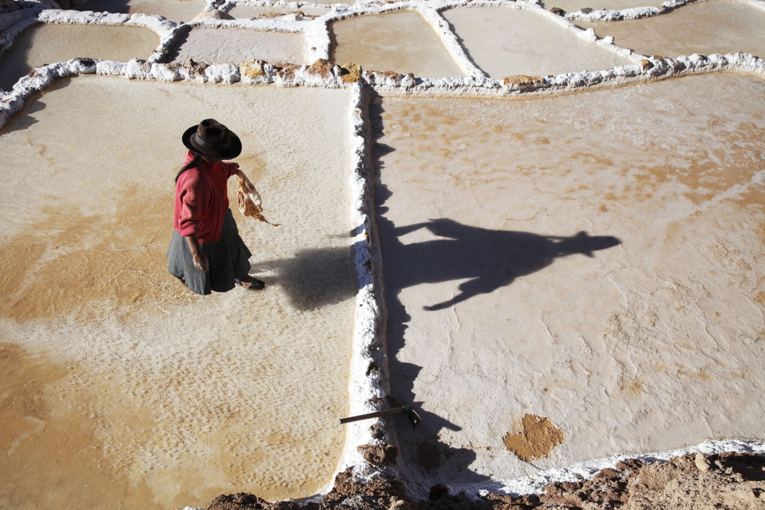 A Quechuan lady walks across the ancient salt pans on Salinas de Maras casting a long shadow. Built by the Inca's this UNESCO status site is still used to produce salt by members of the Maras community. Maras, Peru.