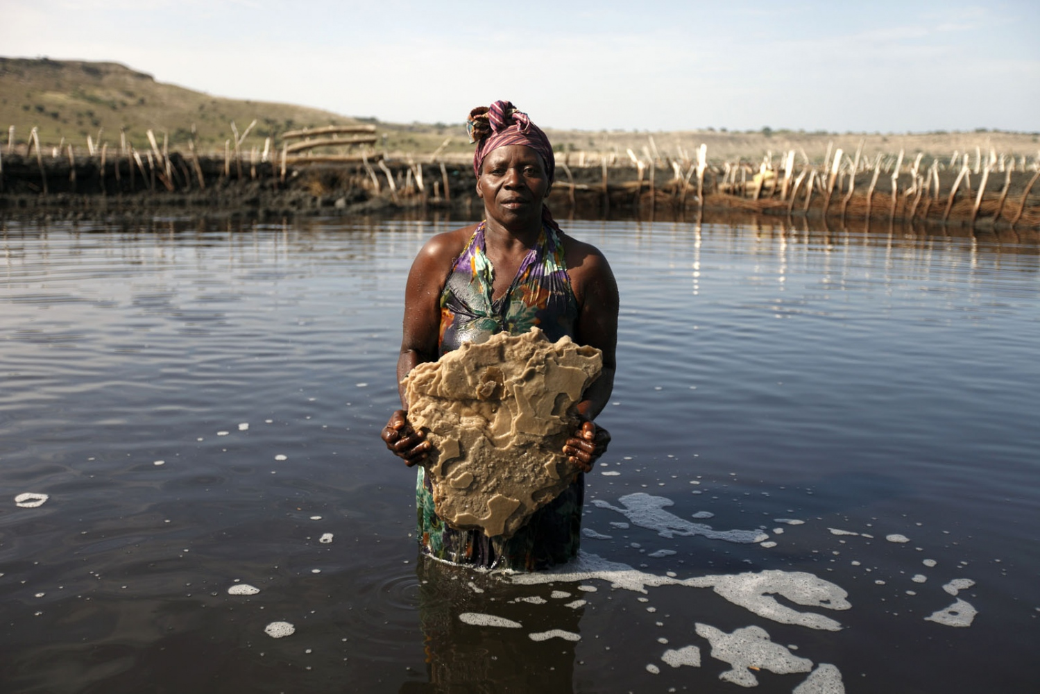 A salt worker holds a huge slab of salt she pulled out of Lake Katwe in Western Uganda. The lake sits in an extinct volcano and the salt forms at the bottom of the lake where it must be broken in to manageable sized pieces and brought to the surface. Full of pollutants and blistering heat makes working in the lake very hard. Katwe, Uganda.
