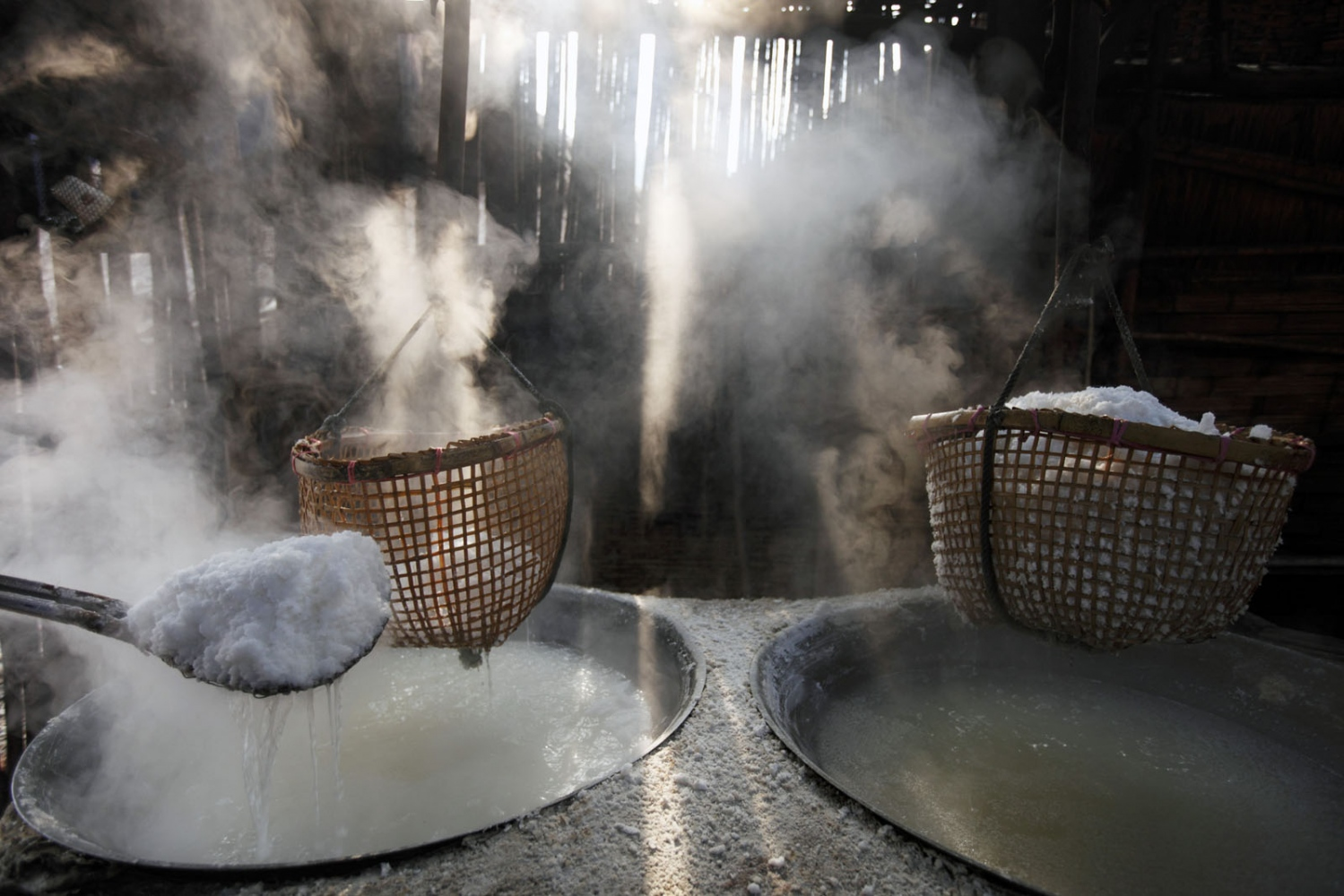 Newly produced salt is scopped out of the hot pans in to a basket hanging above. Here the salt is left to drain. THis process has changed little in 800 years. Bo Klua, Nan Province, Thailand.