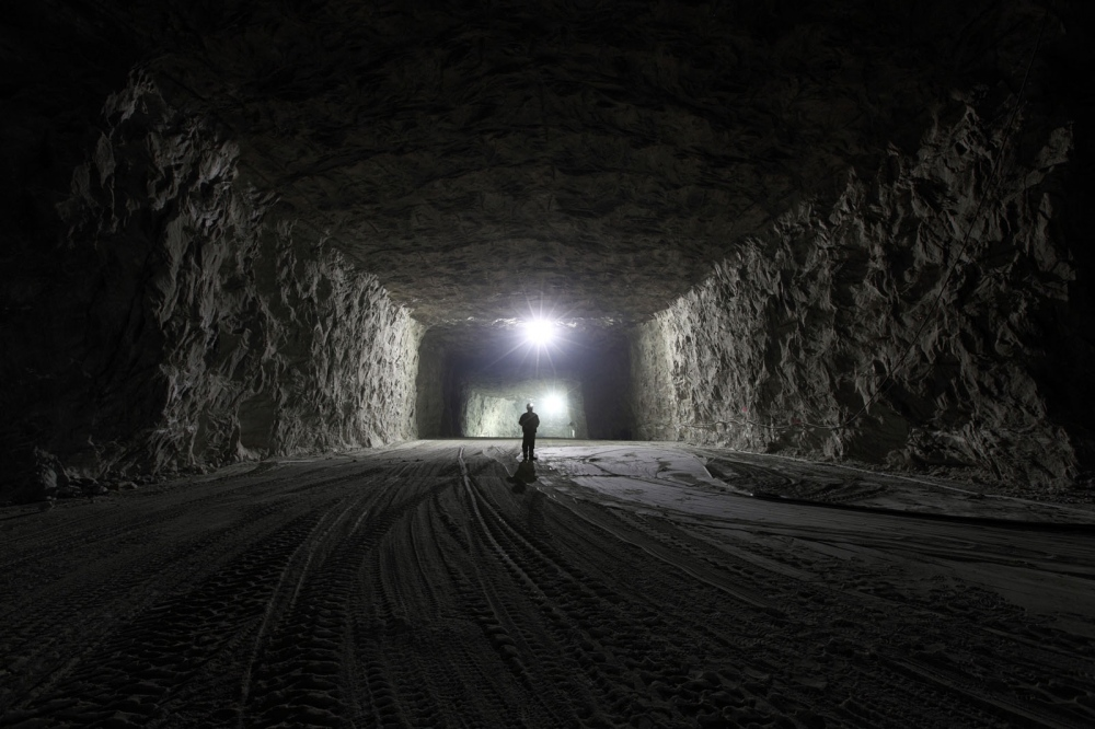 A Romanian miner stands inside the vast mine shafts of the Mihai Salt Mine in Slanic town. Everything from the floor to ceiling is made of salt.