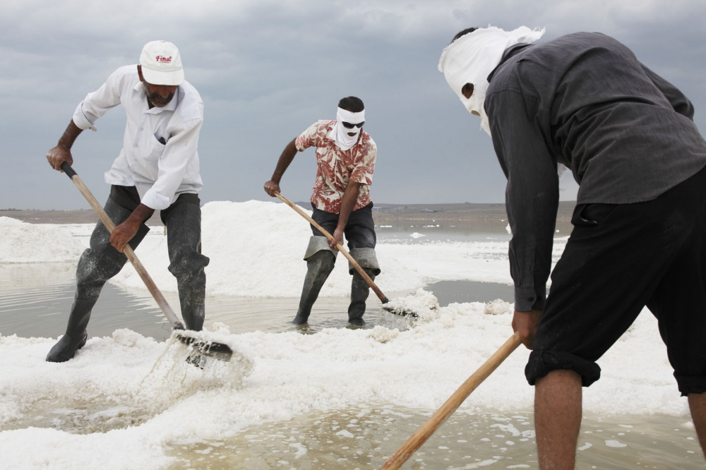 Workers wear face masks to protect themselves from the sun at Binagadi Lake, a large salt lake close to the town of Masazir in Azerbaijan.