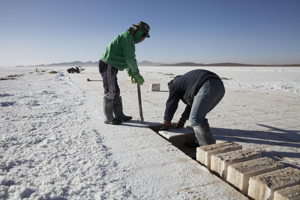 Salt workers use a saw to cut out salt bricks from the salt crust on the Salar de Uyuni, Bolivia.