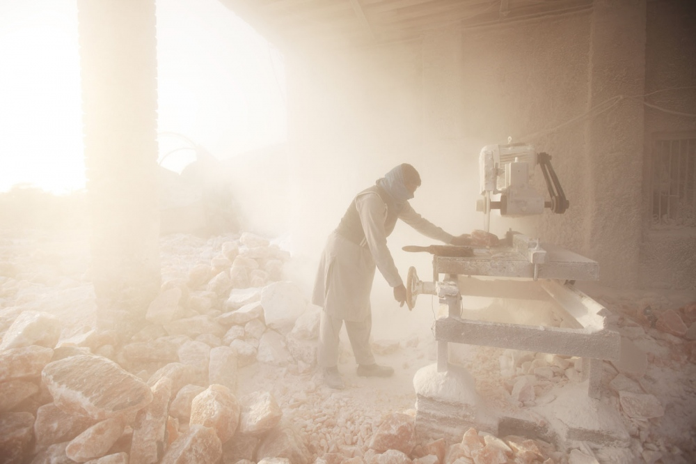 Cutting the pink rock salt at the Khewra Salt mine sends plumes of fine salt dust in to the air. Pakistan.