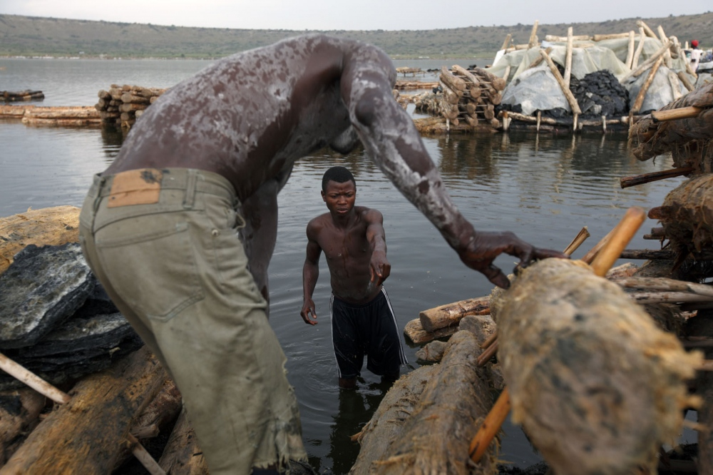 Ugandan salt workers unload the salt they have collected from the bottom of Katwe Lake at the end of the day.