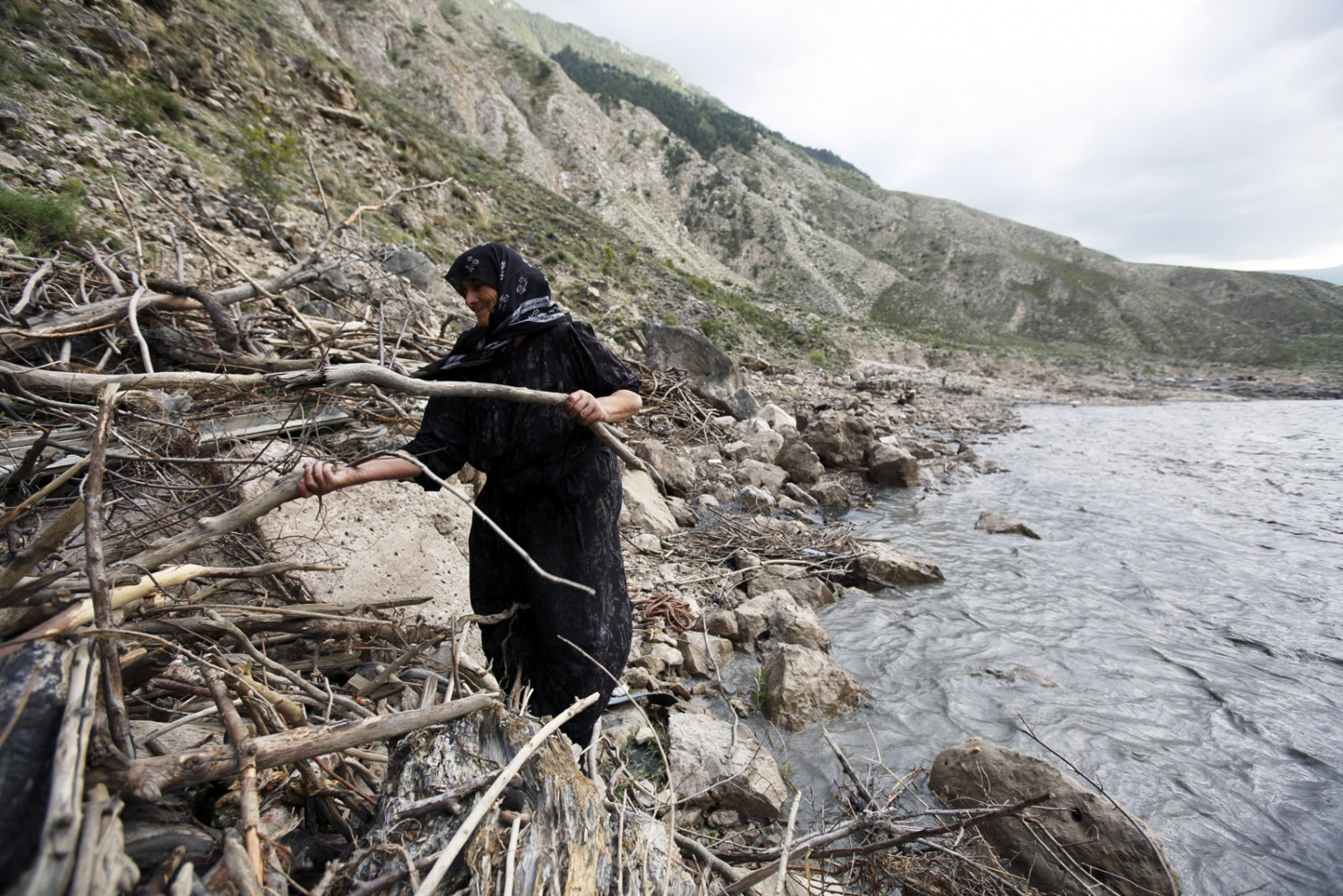 A women, member of one of the last remaining salt making family from Kvankhidatli village, walks to collect drift wood to cook the salt as logging trees is now illegal in the region and most have been cleared due to the salt activity over the years. Botlikhsky District of Dagestan, Russia.