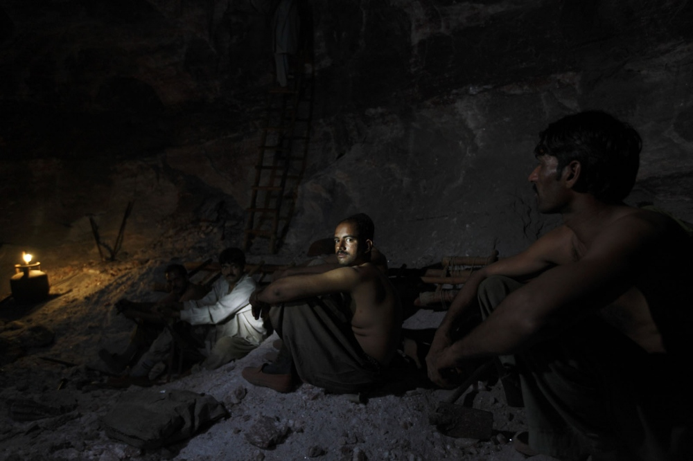 A salt miner in Pakistan's Khewra mine takes a break in the darkness. Punjab, Pakistan.