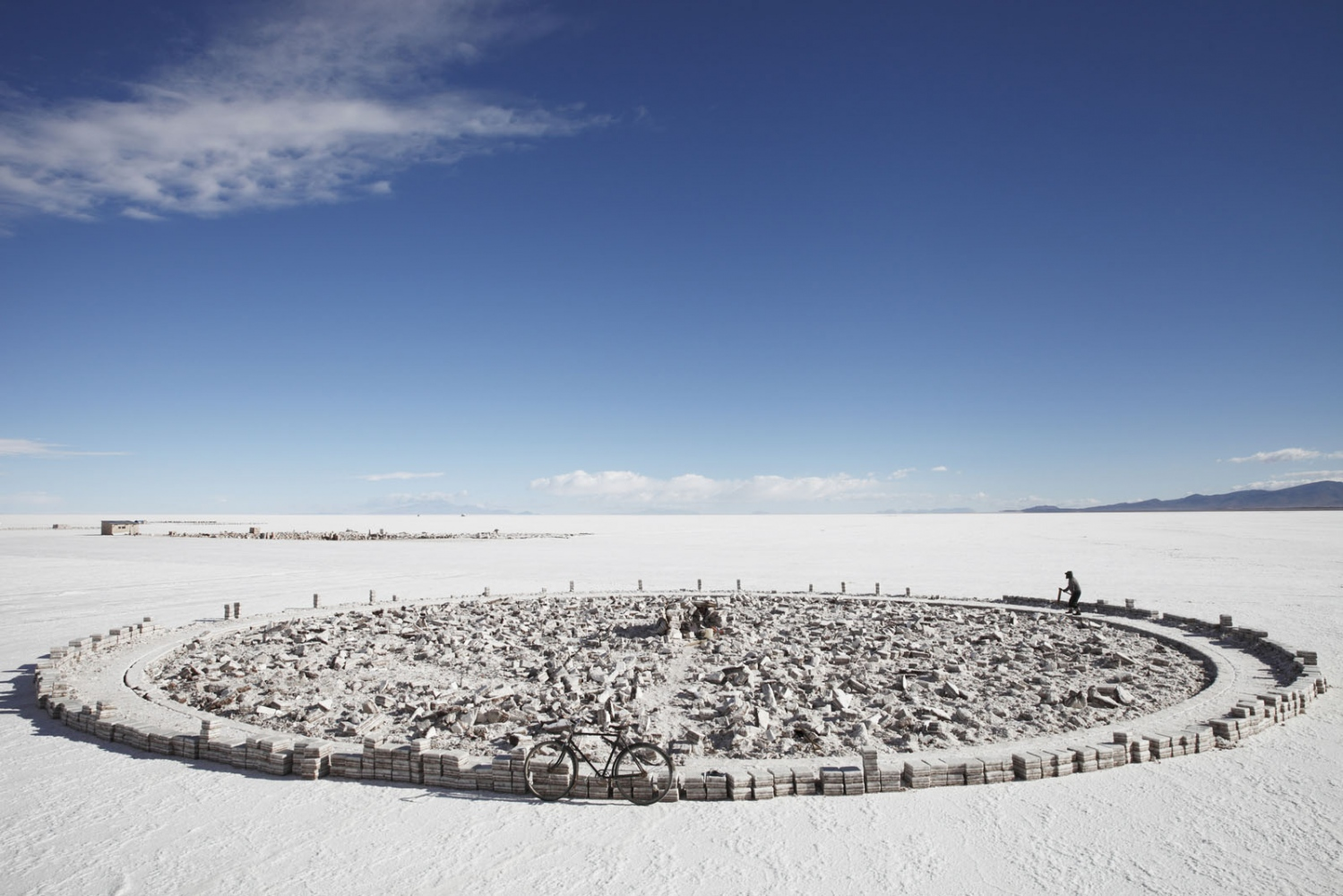 A salt maker cuts salt blocks directly from the world's largest salt deposit in a circular formation. The Salar de Uyuni in Bolivia is the world's largest salt deposit.