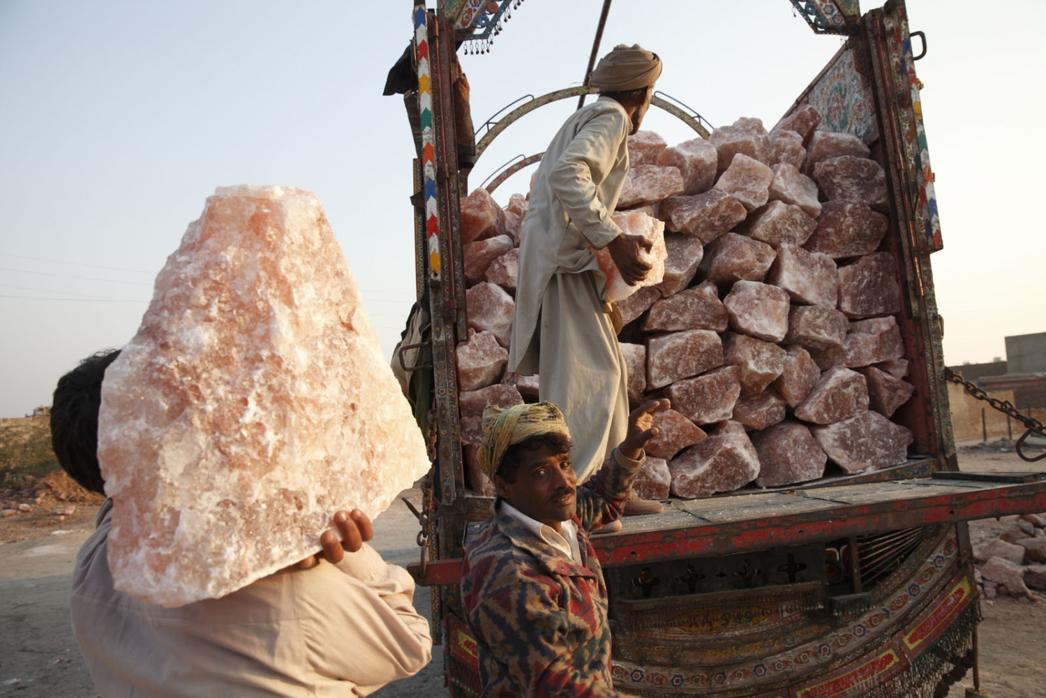 Pakistani salt workers load large pieces of pink rock salt to a waiting truck. Khewra, Punjab.