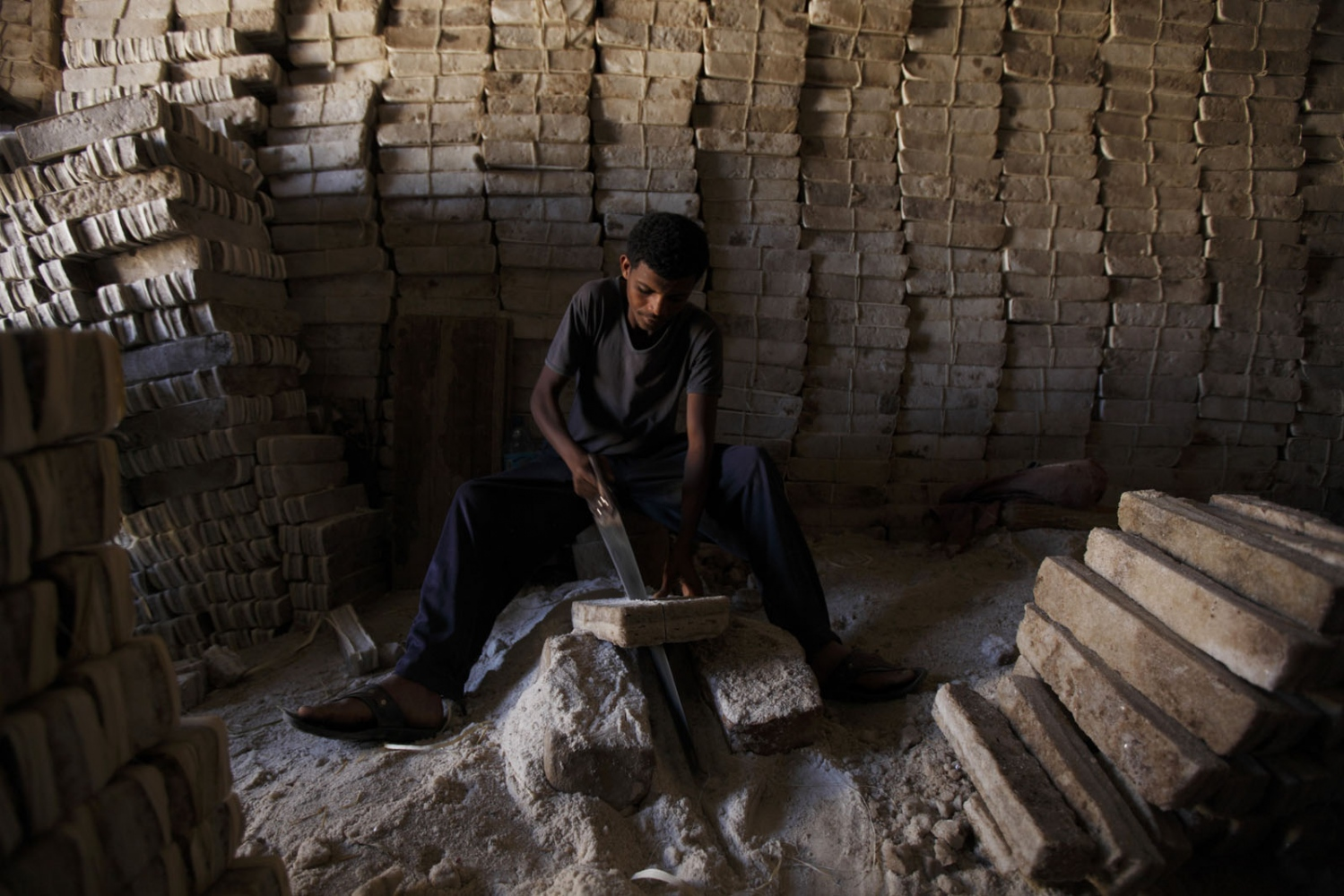 In a shop that sells salt bricks brought by camel from the Danakil Depression uses a saw to cut them in to smaller pieces. Tigray, Ethiopia.
