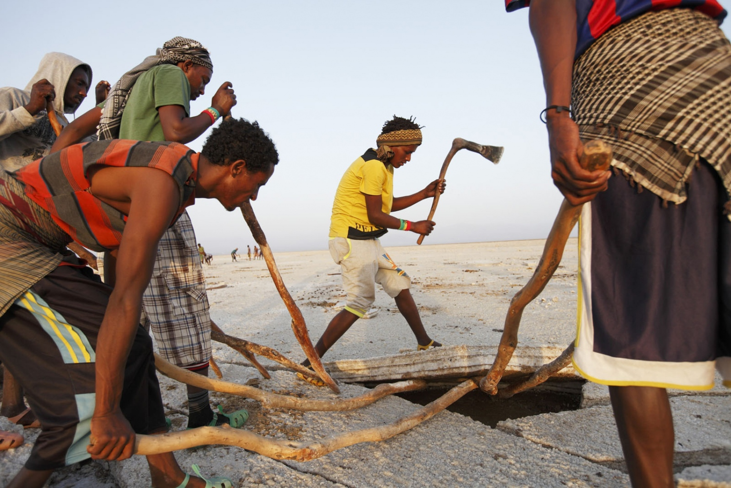 Salt workers literally cut the salt from the ground in the Danakil Depression. The depression is the lowest and hottest inhabited place on our planet and workers must work in very high temperatures with no cover. Afar, Ethiopia.