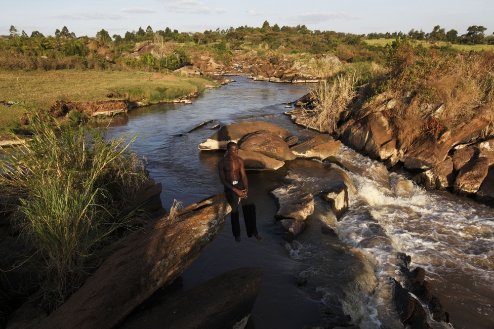 A salt maker sits and relaxes above the Nzoia River in Western Kenya. The river is where he finds special reeds from which he uses to make salt. This special grass is used to make salt by burning it and filtering the ashes. Before mass produced salt arrived in this region many local villagers used this method to make their own salt.