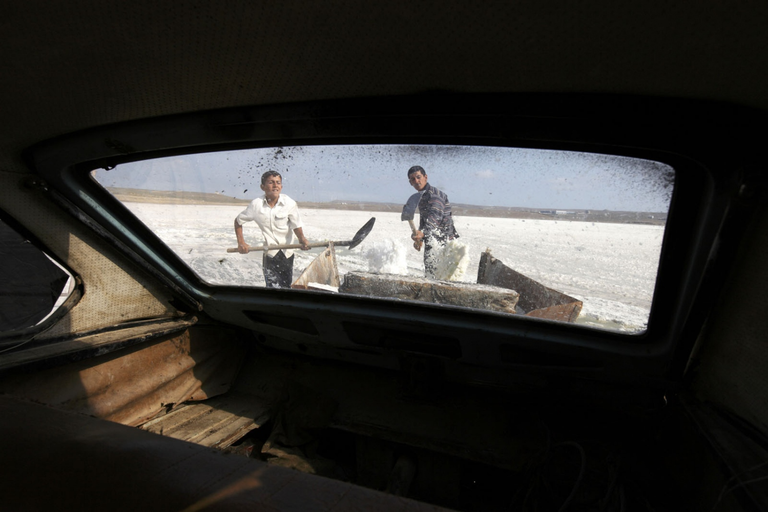 Two brothers load salt from Lake Binagadi in to a trailer attached to the back of a rusty Soviet-era car in Azerbaijan.