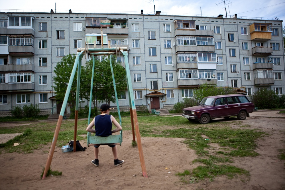 A young boy sits on a swing outside of his building in the small town of Zaton, located outside of Syktyvkar, Russia.