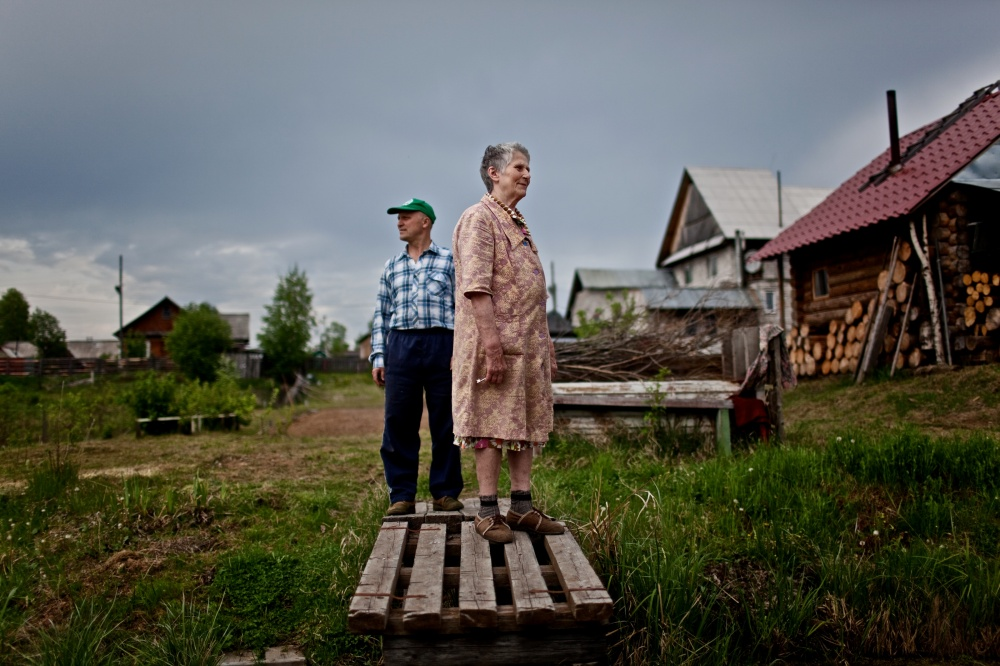 Korukaeva Aliza Ignatievna , 80 years old, and her son Evgeniy stand in the front yard of their home in Zaton, Russia. Korukaeva was exiled with her family to the Komi Republic from Ukraine because of dispossession of the kulaks in 1933.