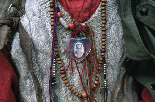 A Tibetan pilgrim wears a pendant of the Dalai Lama during a pilgrimage to a remote sacred mountain. Yunnan Province, China.