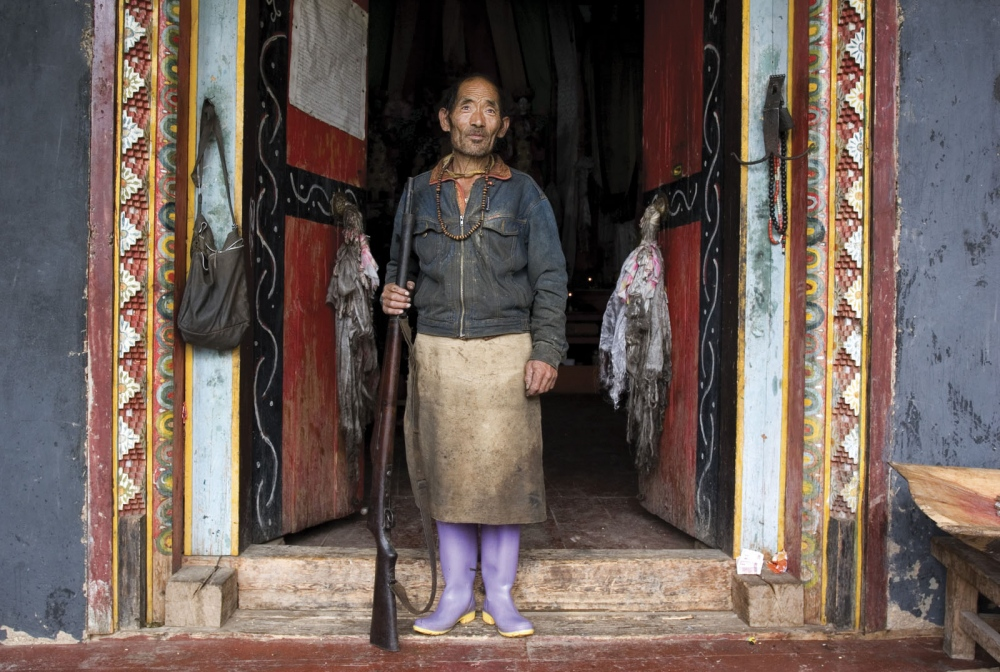 The gate keeper of a remote temple in the mountains of Deqin County. Yunnan Province, China