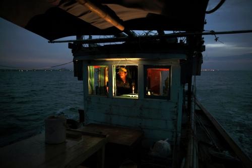 A trawler fising boat captain steers his boat at sea at dawn. Rayong, Thailand.
