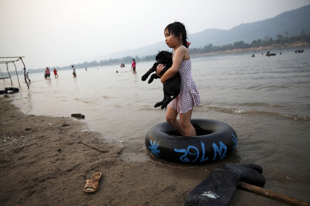A girl plays with her pet dog on a remote beach across the Mekong from Laos. Very few Thais eat dog and most are against the trade. Bueng Kan Province, Thailand