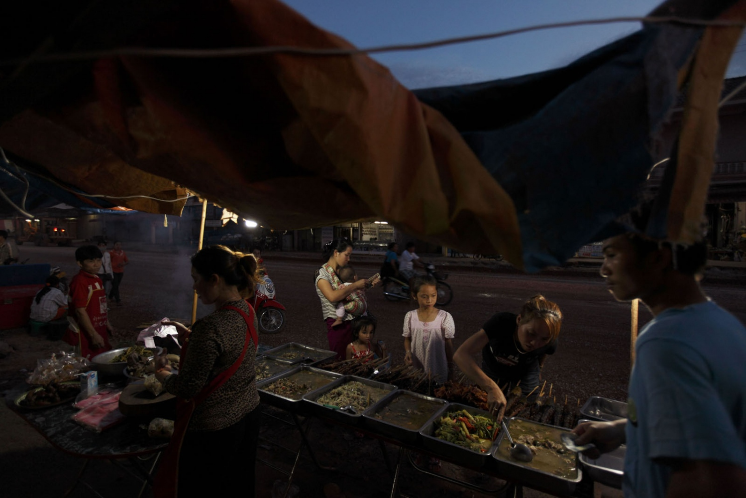 A street stall selling Laos food on the highway running to Vietnam. Trucks laden with dogs pass through this small town every week.Lak Sao, Laos