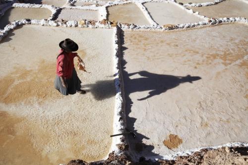 A salt maker wals across a terrace on the Inca made Salinas de Maras in Peru.