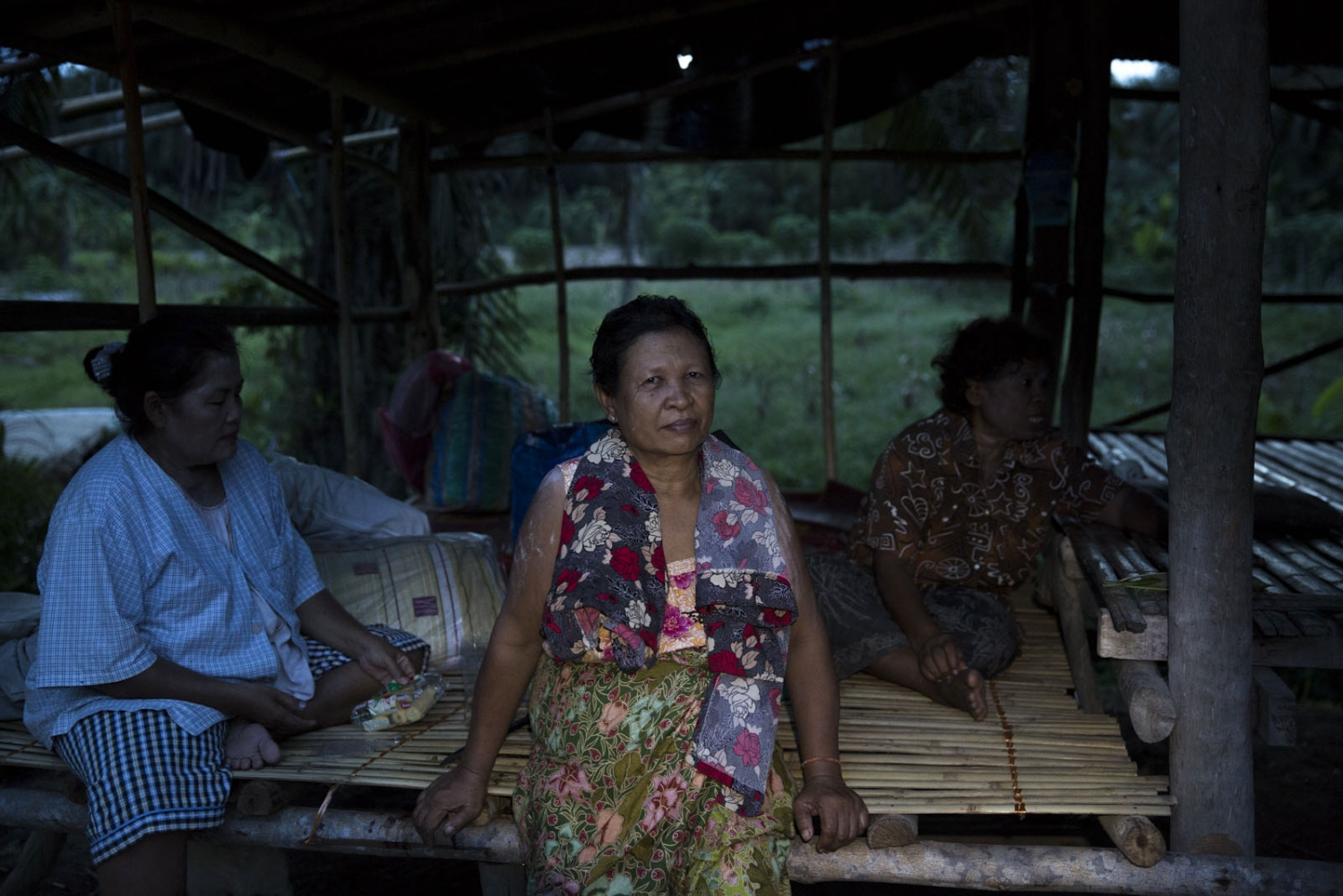 Sommay Sangsom, 62, sits in one of four security look out posts. The villagers take it in turns sleeping in the simple bamboo hut, sleeping 3-4 people per post.