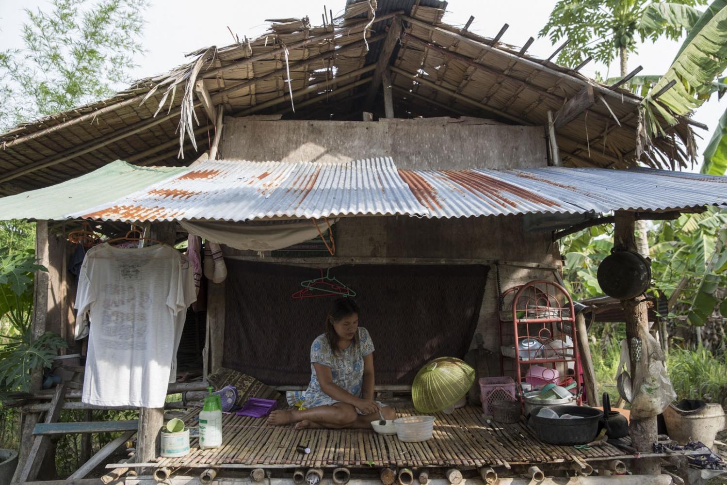 A young women has breakfast alone outside her samll house in Klong Sai Pattana village.